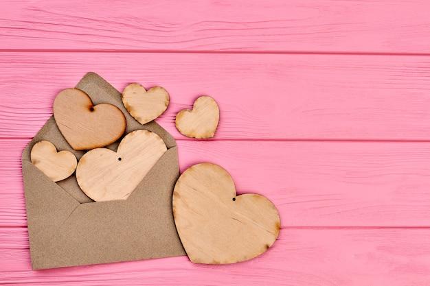 Corações de madeira compensada, envlope e espaço de cópia. corações de madeira em branco com buraco e envelope em fundo de madeira colorido, espaço de texto.