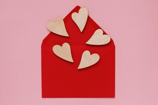 Corações de madeira em um envelope de papel vermelho