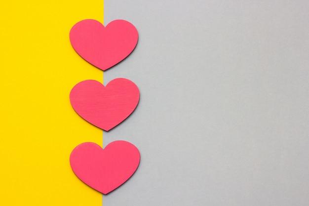 Corações de madeira em um fundo multi-colorido, vista superior