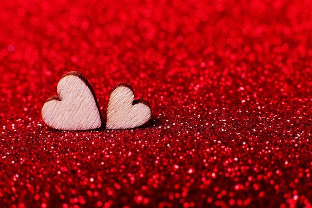 Corações de madeira no fundo brilhante vermelho brilhante para uma decoração festiva