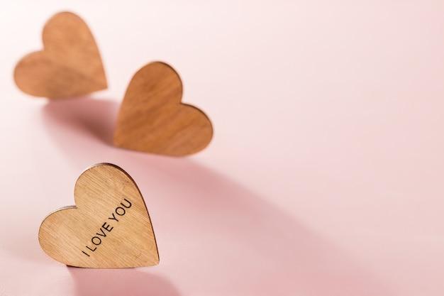 Corações de madeira no fundo rosa