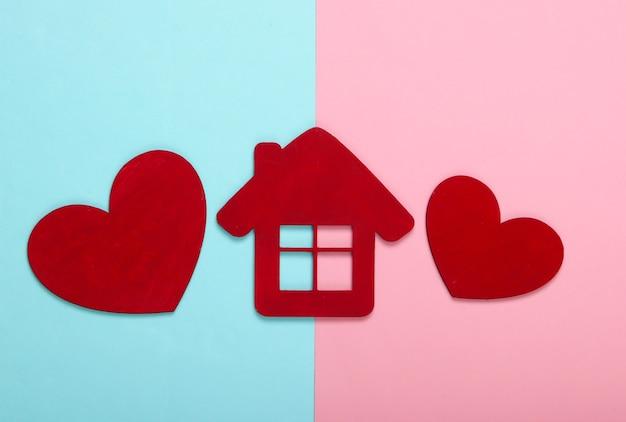 Corações de madeira vermelhos com uma estatueta de casa em rosa pastel azul