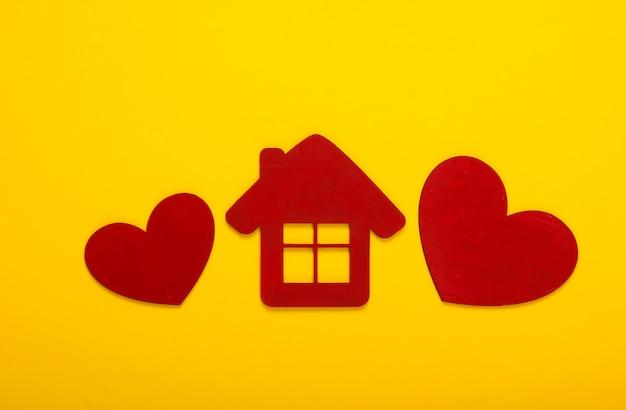 Corações de madeira vermelhos com uma estatueta de casa em um amarelo