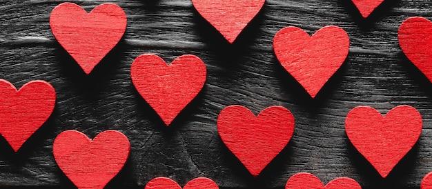 Corações de madeira vermelhos em um fundo preto de madeira.