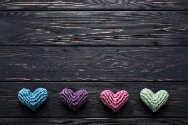 Corações de malha coloridas na mesa de madeira cinza rústica.