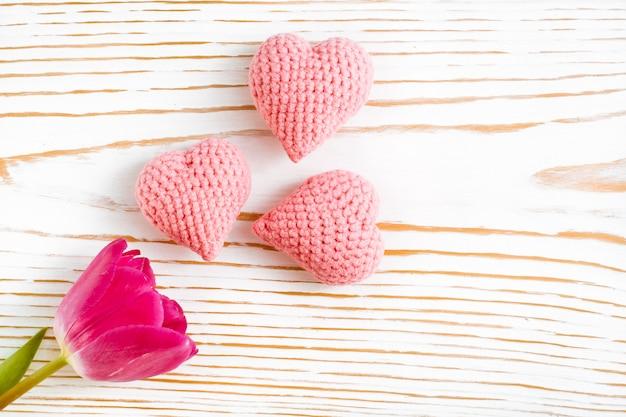 Corações de malha e tulipa rosa em uma madeira branca, vista superior