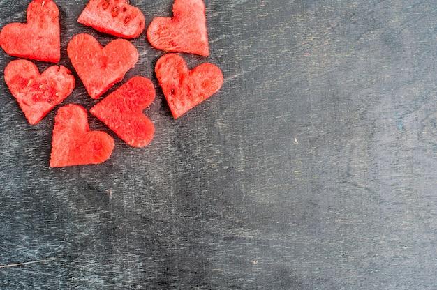 Corações de melancia no fundo de madeira velho. configuração plana