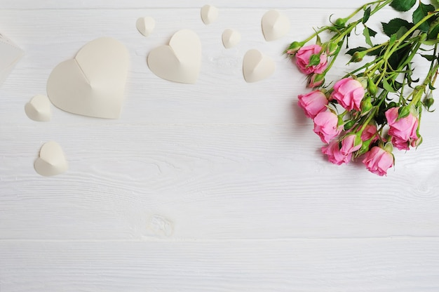 Corações de origami branco de maquete de papel com rosas cor de rosa, cartão de dia dos namorados. camada plana, vista superior