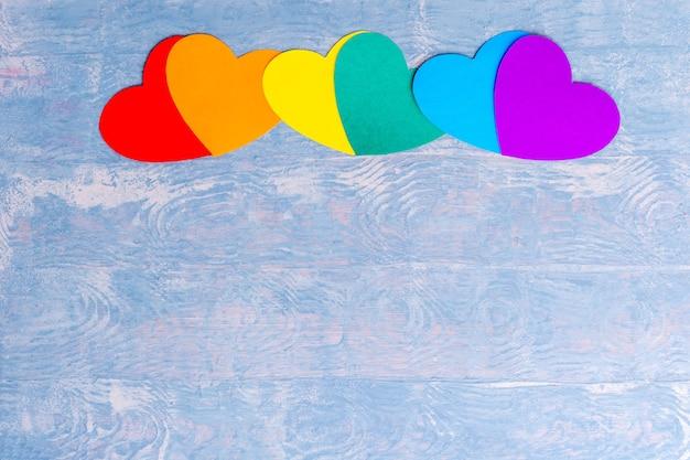 Corações de papel artesanal em cores lgbt alinhados em uma linha sobre fundo azul de madeira