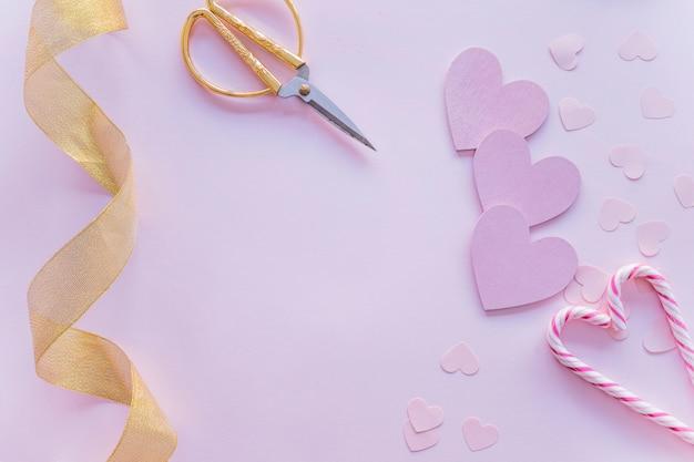 Corações de papel com bastões de doces na mesa