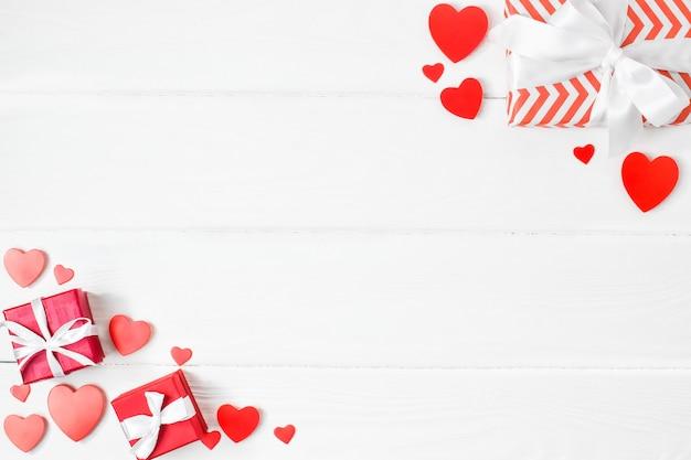 Corações de papel com presentes colocados nos cantos. vista da embalagem da bancada e feliz dia dos namorados