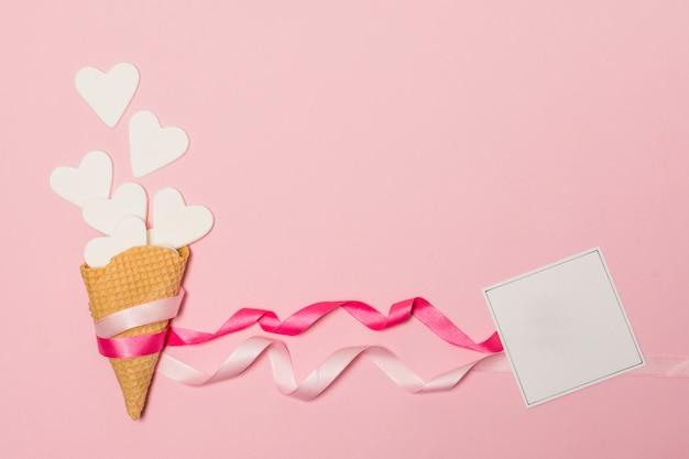 Corações de papel em bastões de waffle perto de cartão postal