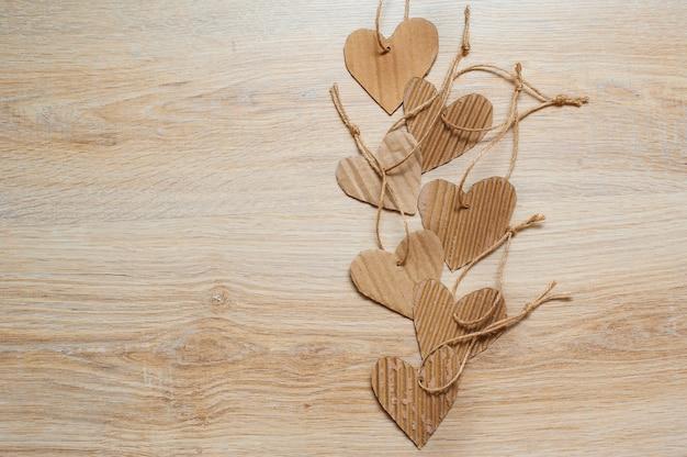 Corações de papel kraft feito à mão na textura de madeira.