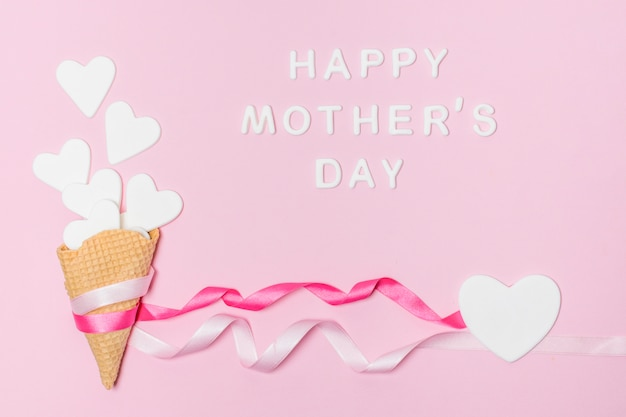 Corações de papel nas bengalas de waffle perto do título do dia das mães feliz