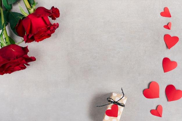 Corações de papel perto de caixa de presente e flores