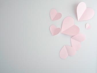 Corações de papel rosa colocados no fundo branco.