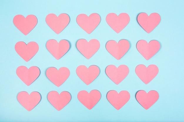 Corações de papel rosa sobre fundo azul. corações de corte de papel dispostos em linhas sobre fundo azul. configuração plana