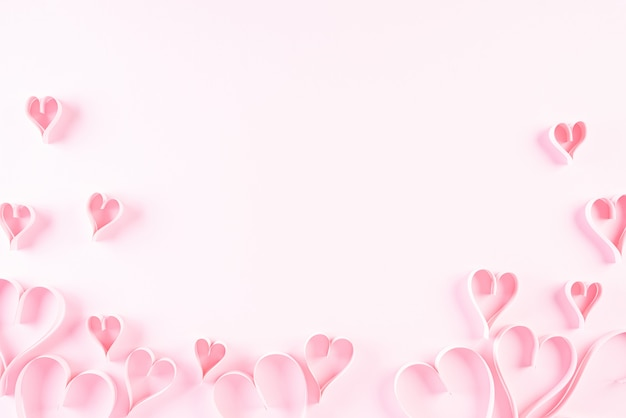 Corações de papel rosa sobre fundo de papel rosa, amor e conceito de dia dos namorados.