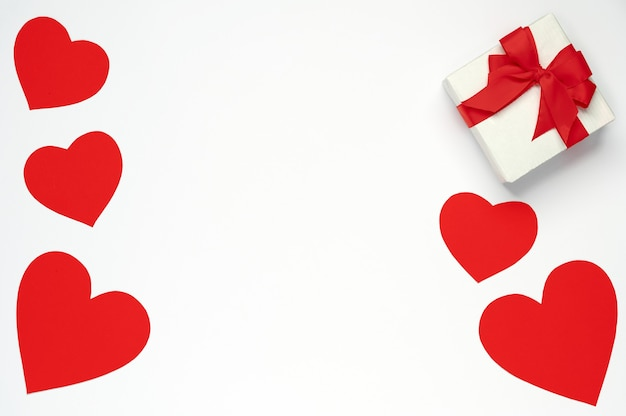 Corações de papel vermelho com caixa de presente em fundo branco isolado. vista superior, configuração plana. modelo de dia dos namorados