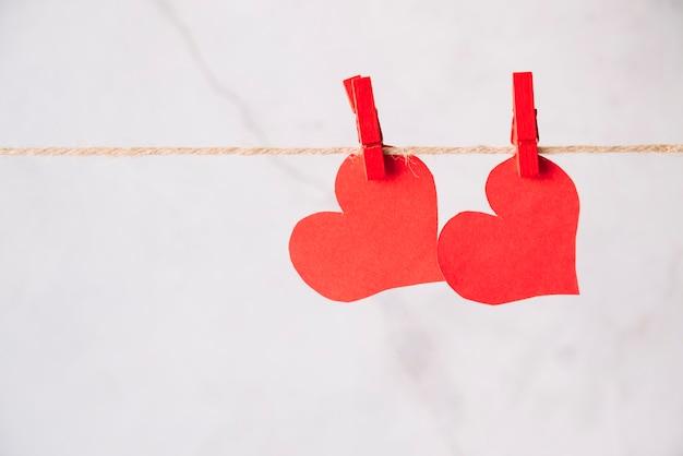 Corações de papel vermelho com pinos de engate no segmento