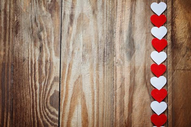 Corações de papel vermelho e branco no varal de madeira backgrou