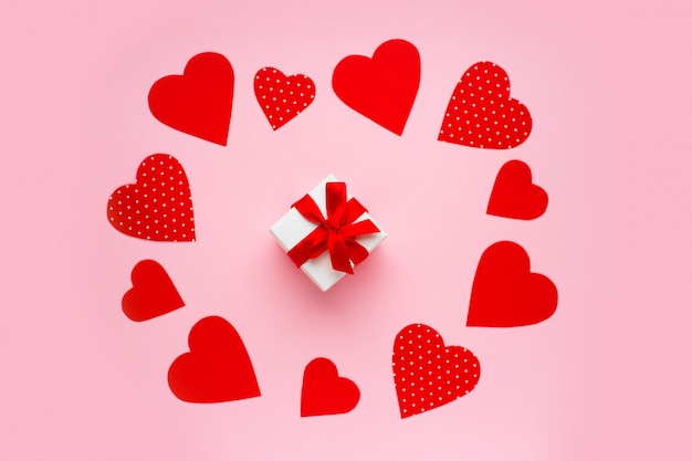Corações de papel vermelho em torno de uma caixa de presente em rosa. feliz dia dos namorados conceito.