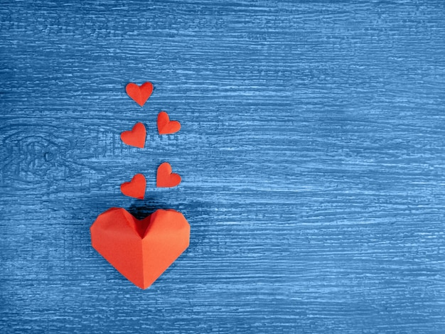Corações de papel vermelho em um velho, azul, texturizado, de madeira.