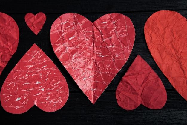 Corações de papel vermelho na superfície preta