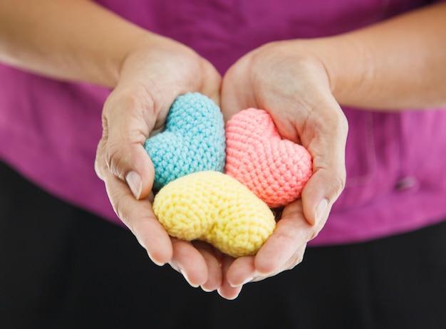 Corações de tricô multicolor coloridas realizada por ambas as mãos da fêmea, representando a mão amiga