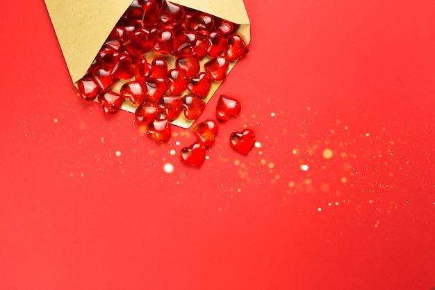 Corações de vidro saem de um envelope aberto sobre um fundo vermelho.