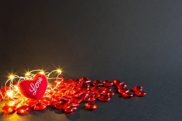 Corações de vidro vermelho e coração de pelúcia macio com as palavras amor em um fundo preto, luzes douradas - dia dos namorados. férias, banner, copyspace. compras e presentes, presente para um ente querido, casal apaixonado