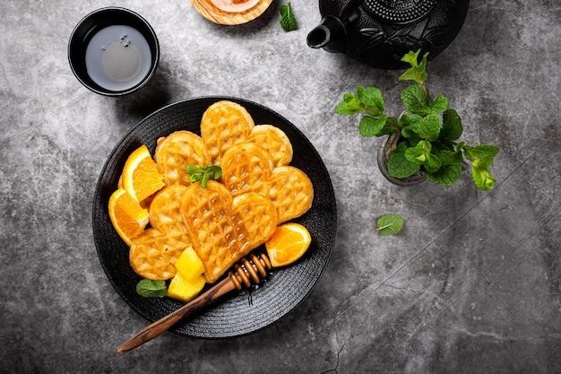 Corações de waffles quentes frescos com fatias de laranja e mel na superfície cinza, vista de cima, plana leigos. conceito de comida de pequeno-almoço saudável