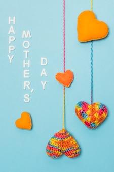 Corações decorativas perto do título do dia das mães feliz