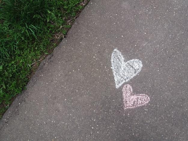 Corações desenhados com giz na calçada de asfalto