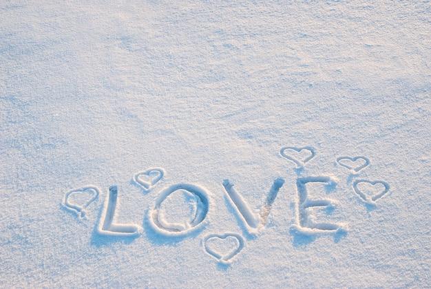 Corações desenhados em smow com a palavra amor