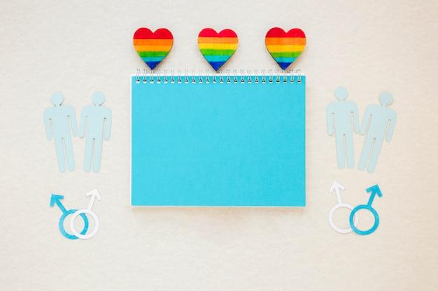 Corações do arco-íris com ícones de casais gays e o bloco de notas