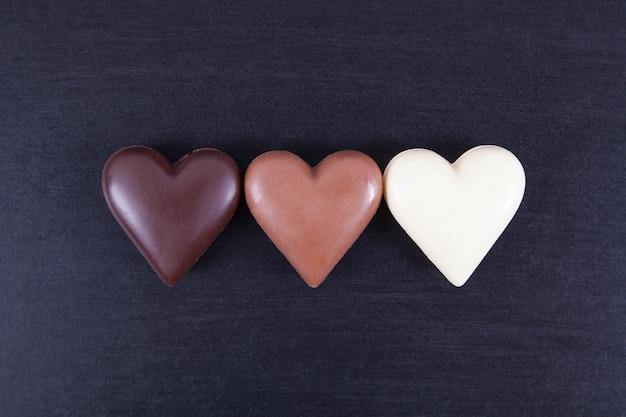Corações do chocolate em um fundo escuro, close-up.