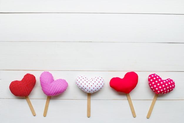 Corações do dia dos namorados em fundo branco de madeira.