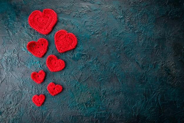 Corações dos namorados de crochê vermelho em fundo escuro.