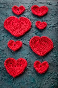 Corações dos namorados de crochê vermelho no bacground branco.