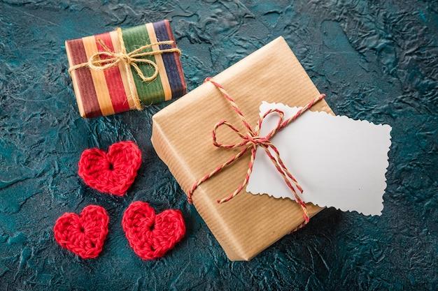 Corações dos namorados em crochê, caixa de presente e um cartão comemorativo em preto