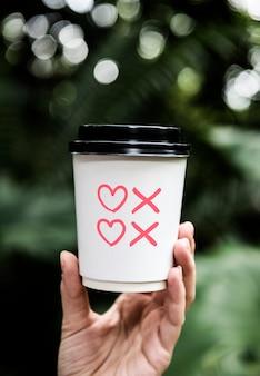 Corações e beijos símbolos em uma xícara de café de papel