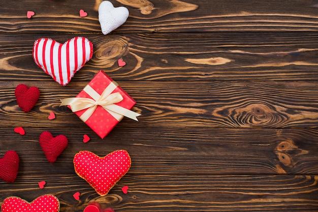 Corações e caixa de presente na superfície de madeira escura