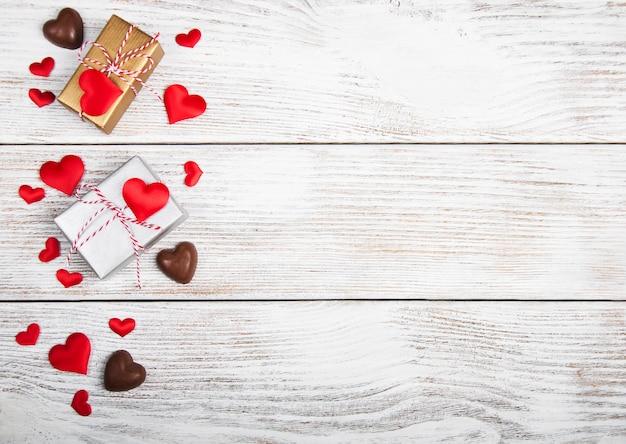Corações e caixas de presente na superfície de madeira