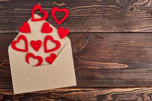 Corações e evelope de papel vermelho, vista superior. envelope e corações abertos, copie o espaço. conceito de férias do dia dos namorados.