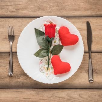 Corações e flores na placa entre talheres