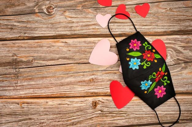 Corações e máscara facial na mesa de madeira. celebração do dia dos namorados em tempos de vírus