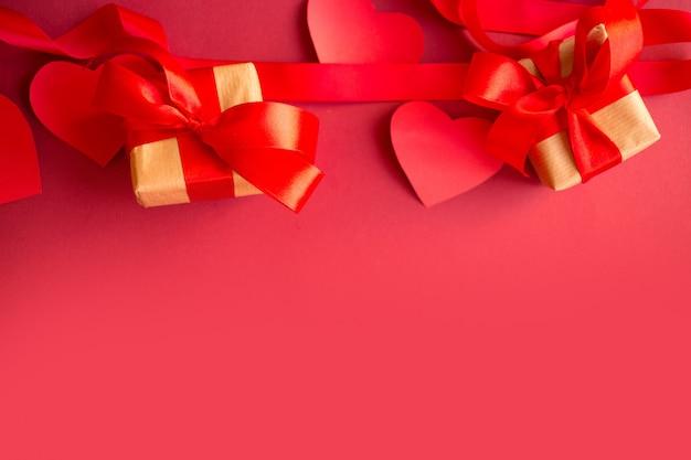 Corações e presentes vermelhos em uma caixa em um fundo vermelho. presente de dia dos namorados