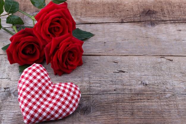 Corações e um buquê de rosas vermelhas na placa de madeira, dia dos namorados