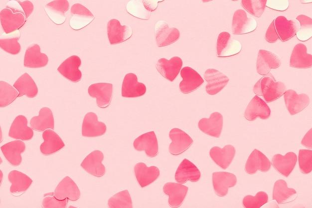 Corações em forma de confetes em fundo rosa pastel.